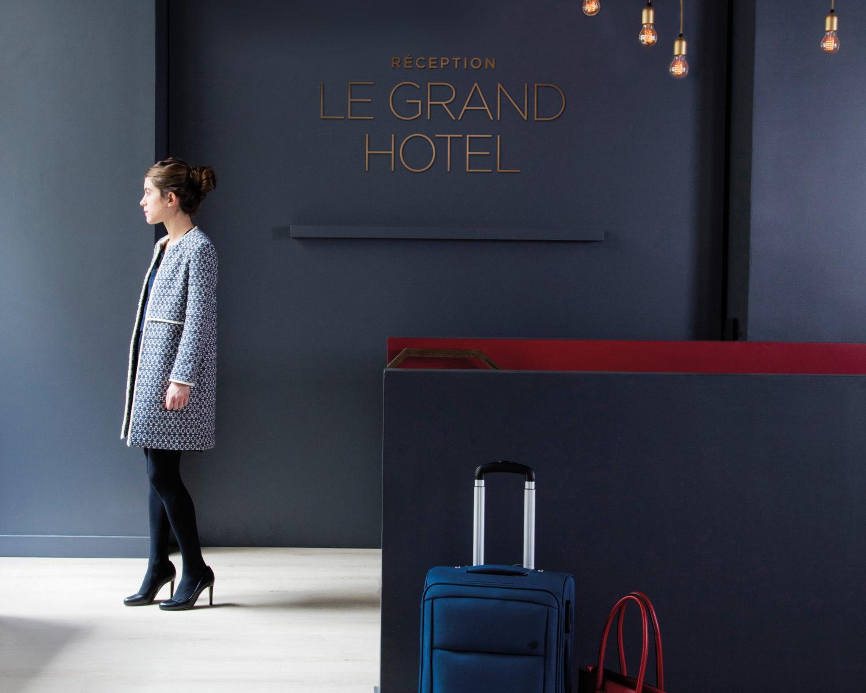 un hall d'hôtel chaleureux avec un parquet BerryAlloc au sol. Un ejeune femme élégante regarde vers l'extérieur