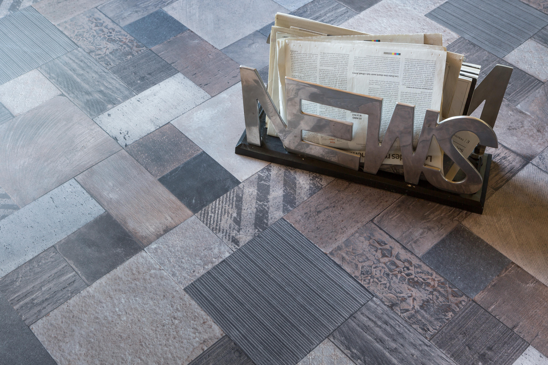 Style industriel : Les sols vinyles ne cessent de se réinventer et cassent les codes en mixant les effets dans un esprit récup' des plus réussis. Ici un mélange d'effets bois, carrelage et ciment réunis dans un même sol prêt à poser.