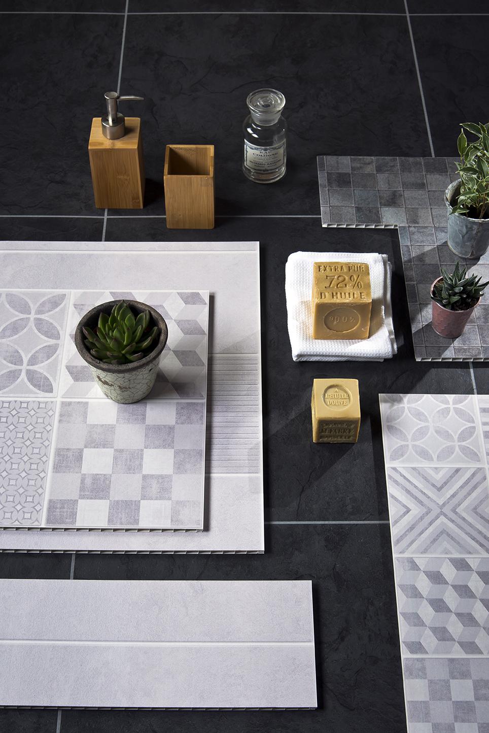 Echantillons de lambris muraux imitation carreaux ciment disposés en pêle même avec quelques accessoires de salle de bains.