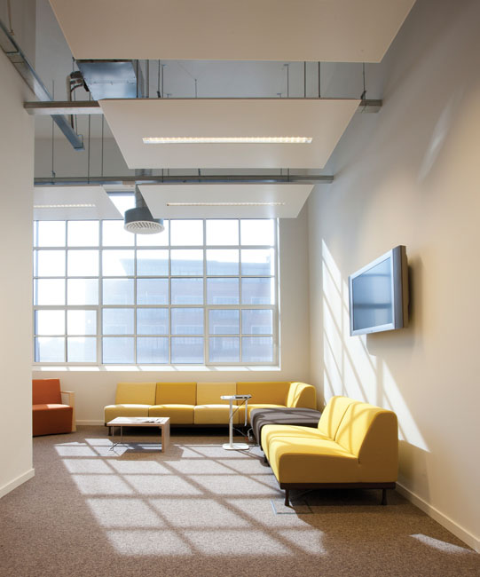 Style industriel : Un salon d'esprit industriel installé dans un loft. Canapés jaunes et lumière à foisons.