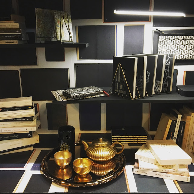 une vitreine avec des livres et un service à thé Mariages Frères en or.