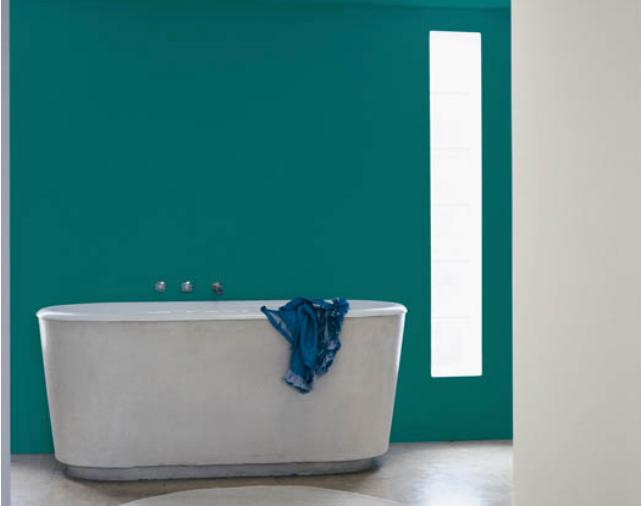 une baignoire très contemporaine blanche sur un mur peint en vert