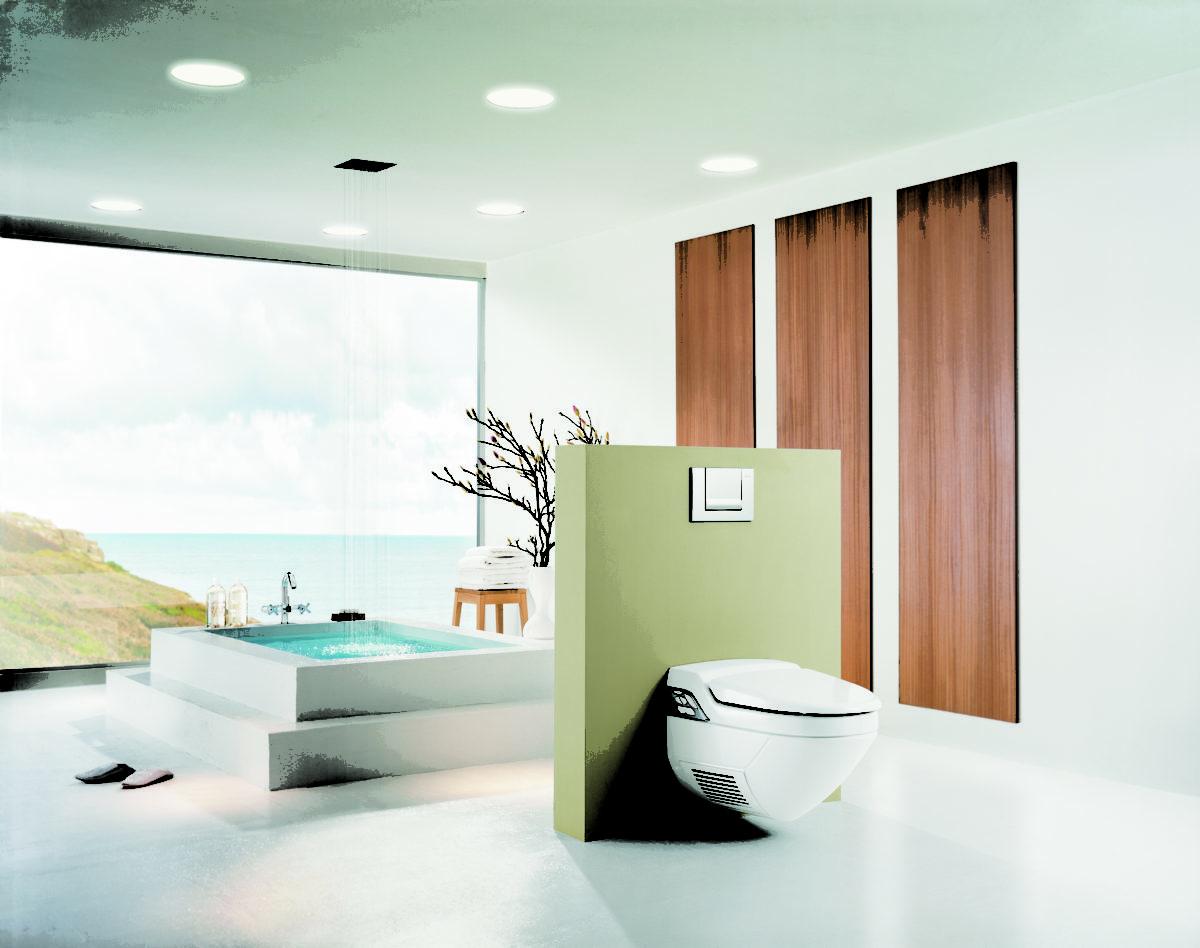 une grande salle de bains avec WC suspendu. Au fond une baie vitrée qui donne sur un paysage de bord de mer.