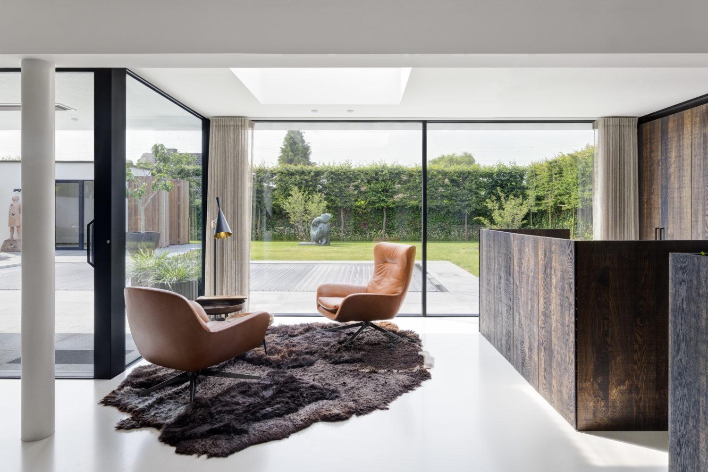 une jolie villa avec large baie vitreé qui donne sur une terrasse. Au premier plan deux fauteuils en cuir et un tapis au sol.e