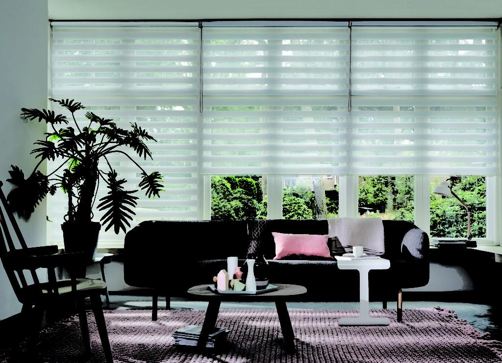 un salon devant une large baie vitreé équipée d'un voile store blanc