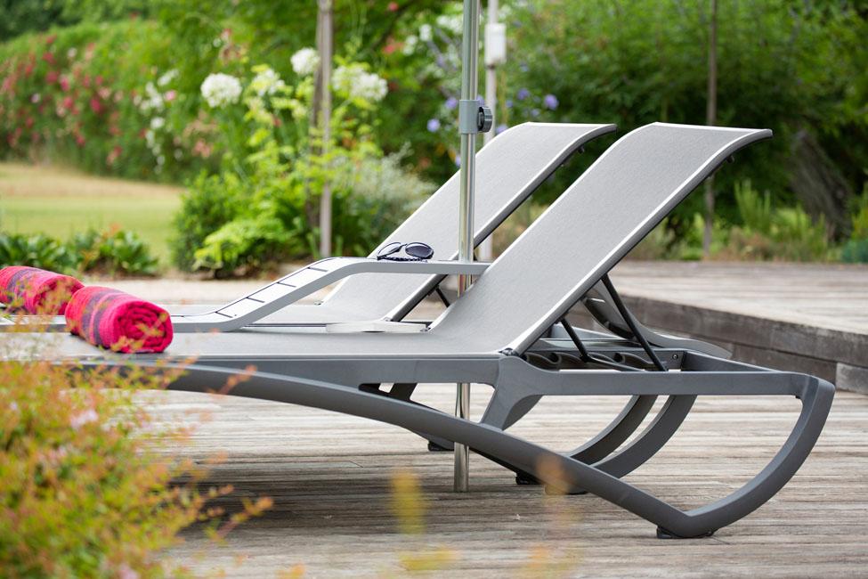 une double chaise longue en bord de piscineinvite à la détente à deux.