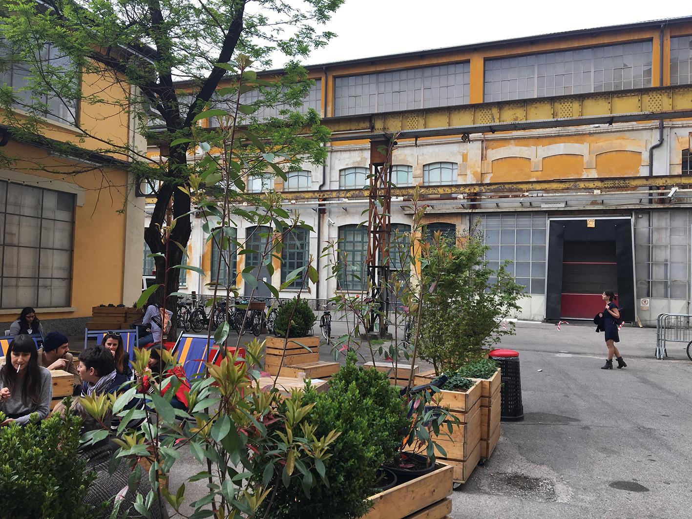 Dans une cour d'anciens batimants industriels, une terrasse de bistrot improvisée reçoit le svisiteurs de la Design Week de Milan