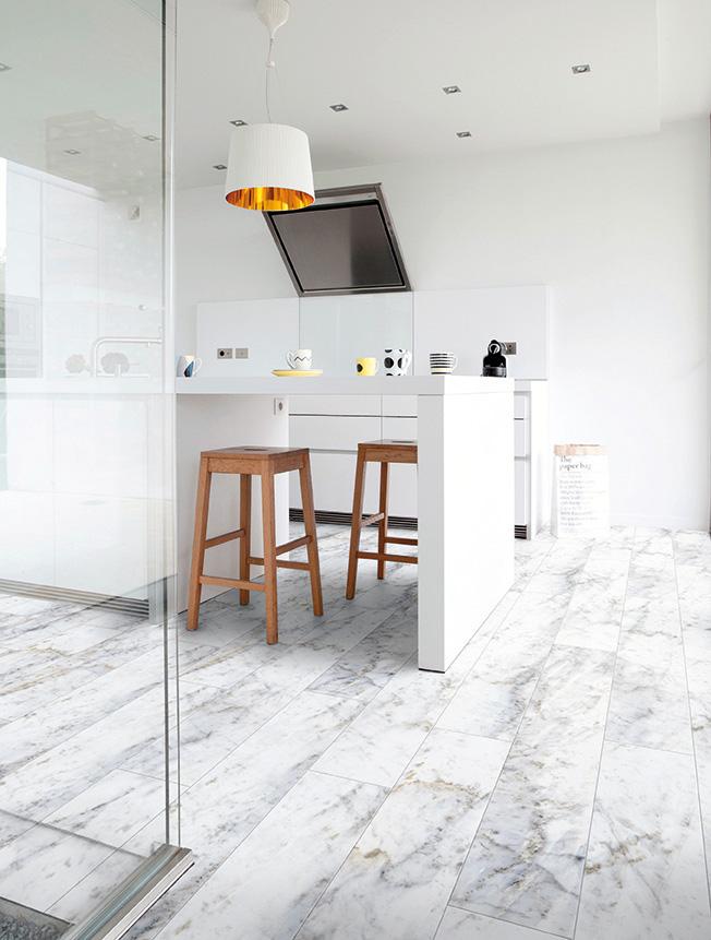 une jolie cuisine contemporaine avec un bar blanc et des mange debout en bois clair. Le sol est décoré de sol Gerflor imitation marbre blanc