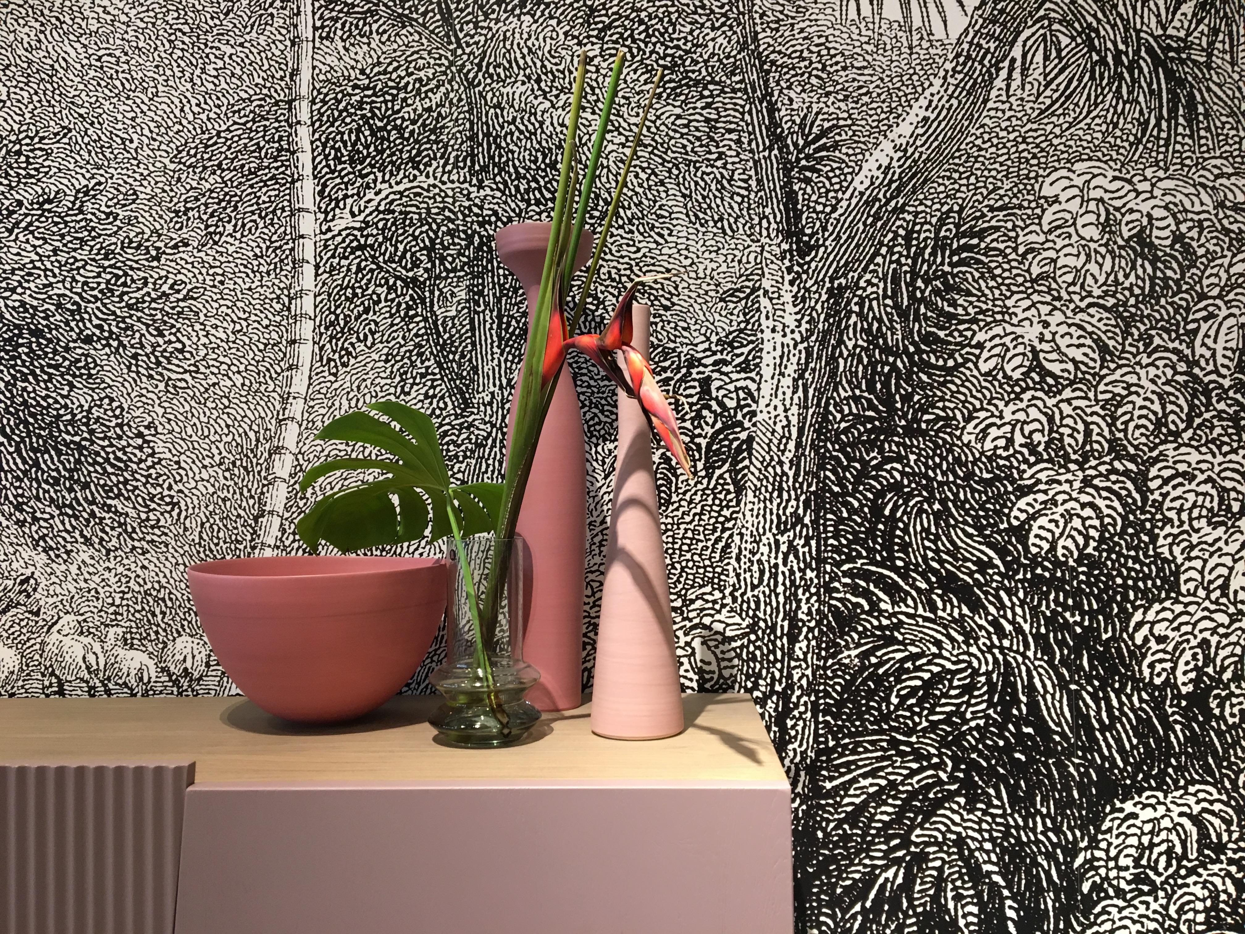 2 vases et une poterie de couleur rose nuancé trônent sur ue buffet laqué rose. Derrière un papier peint esprit jungle en noir et blanc