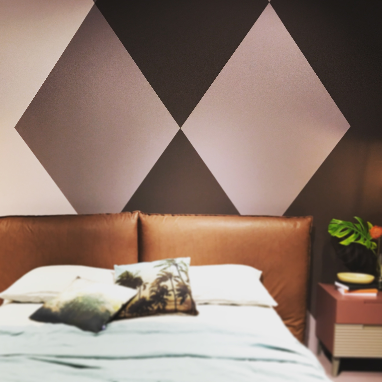 Dans une chambre, derrière une tête de lit en cuir, le mur est peint en garnds losanges de couelur Vieux Rose, Rose poudré et prune.