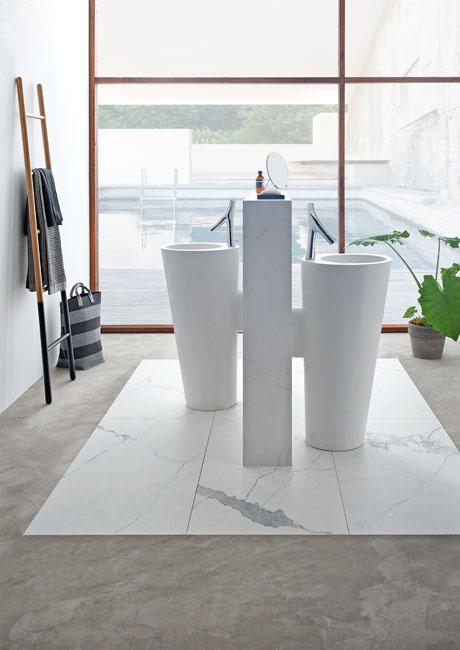 Une salle de bains nouvelle génération avec des colonnes lavabos en marbre de synthèse et un sol qui mixe marbre veiné et béton ciré