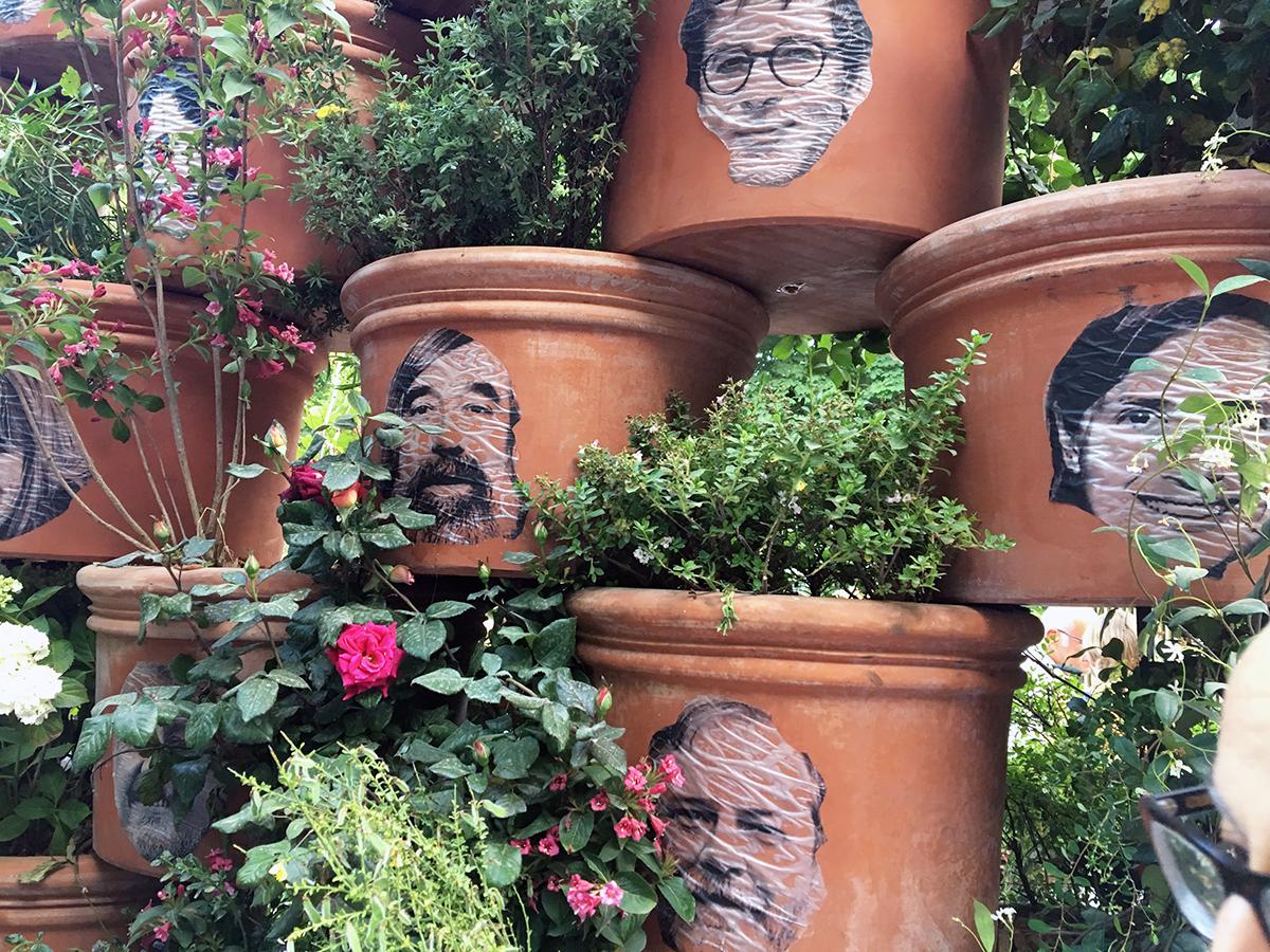 de grandes jarres en terre cuite sont décorés de portraits imprimés sur papier puis collés