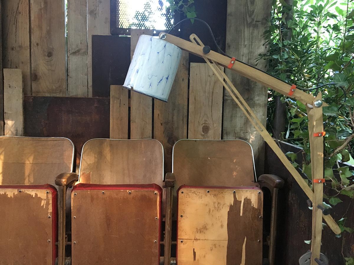 une rangée de strapontins en v-bois et un lamapdaire réalisé avec un pot de fer équipe la artie abritéé d'un jardin.