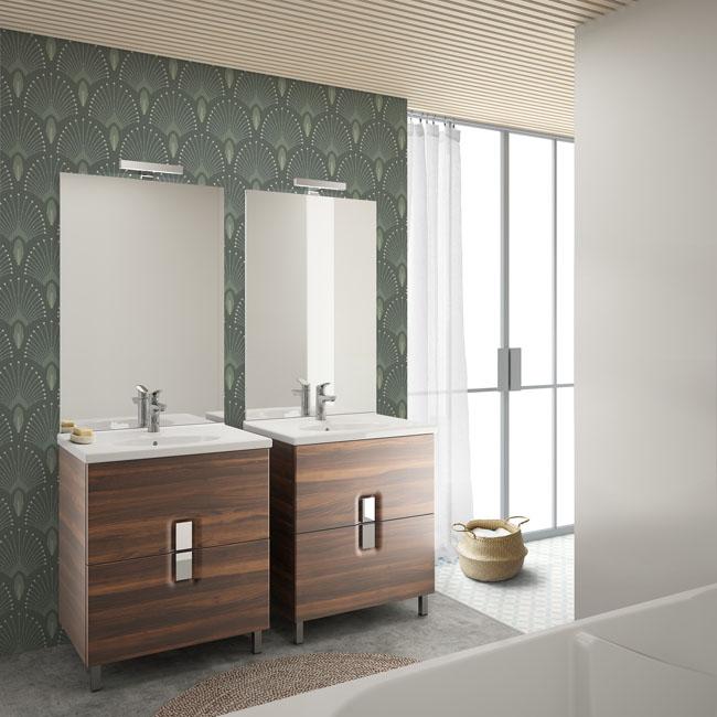 deux meubles vasques en bois sont installés cote à cote devant un joli papier peint vert à arabesques