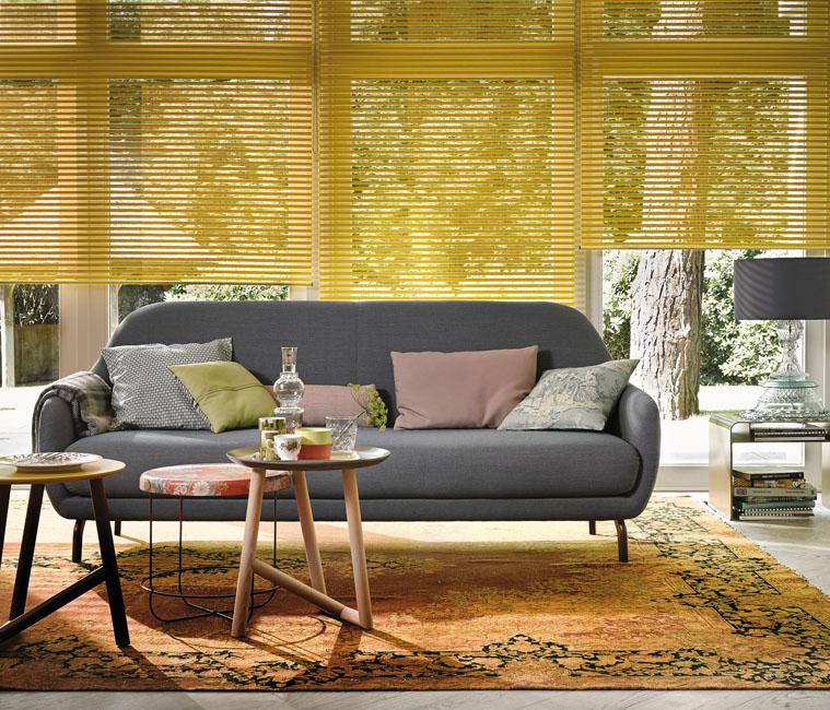 un salon contemporain avec un canapé gris et une grande baie vitrée habillée d'un store jaune moutarde Luxaflex