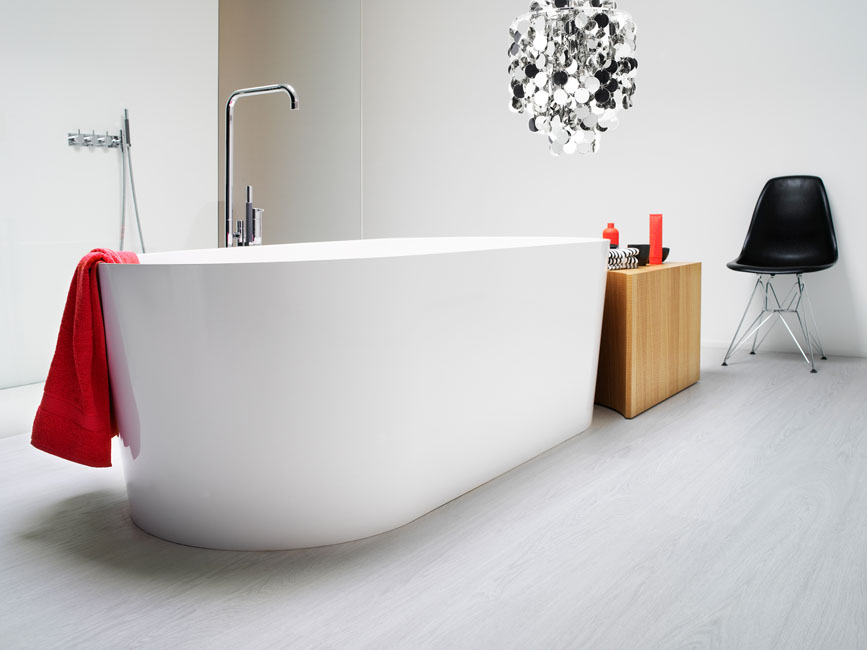 une baignoire blanche très design trône au milieu d'une pièce rvêtu d'un sol stratifié bois clair