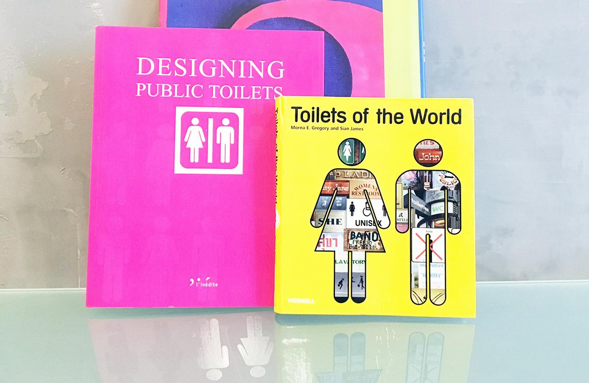 Deux livres sont posés devant un mur gris patiné : Toilets of the world et Designing Public Toilets