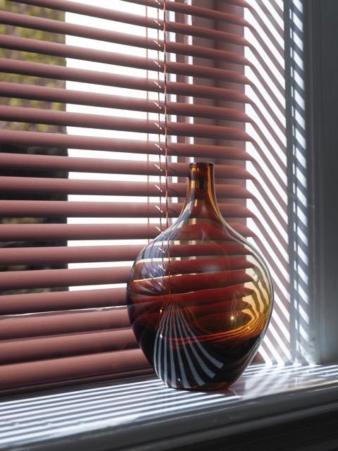 une fenêtre est fermée par un stores vénitens à lames fines laquées couleur vieux rose. Devant un vase transparent et bombé, d'une belle teinte brune.