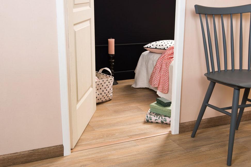 Une teinte pêche sur les murs s'accorde à merveille avec un noir profond. Même la barre de seuil joue l'effet cosmétique avec une teinte abricot à marier avec des plinthes adhésives couleur bois