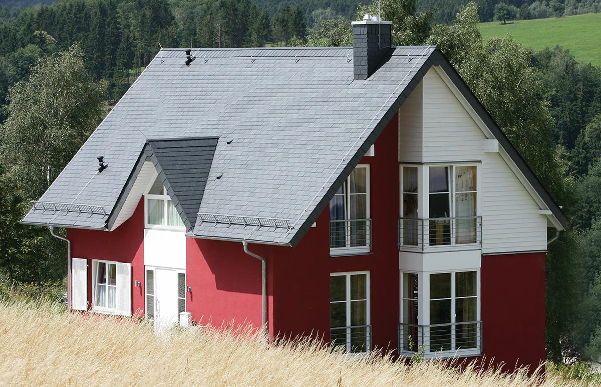 Une belle maison en pleine campagne. Sa façade rouge vif et son toit en ardoise naturelle lui donnent dynamisme et originalité