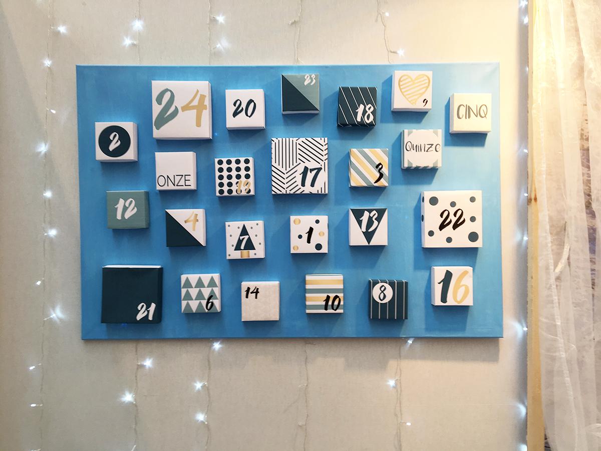Des petites boîtes collés sur un fond bleu vif crée un calendrier de l'avent vif et moderne.