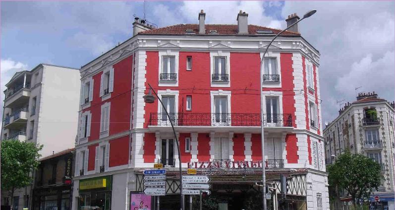 Façade d'immeuble ancien en région parisienne avec une couleur rouge vif