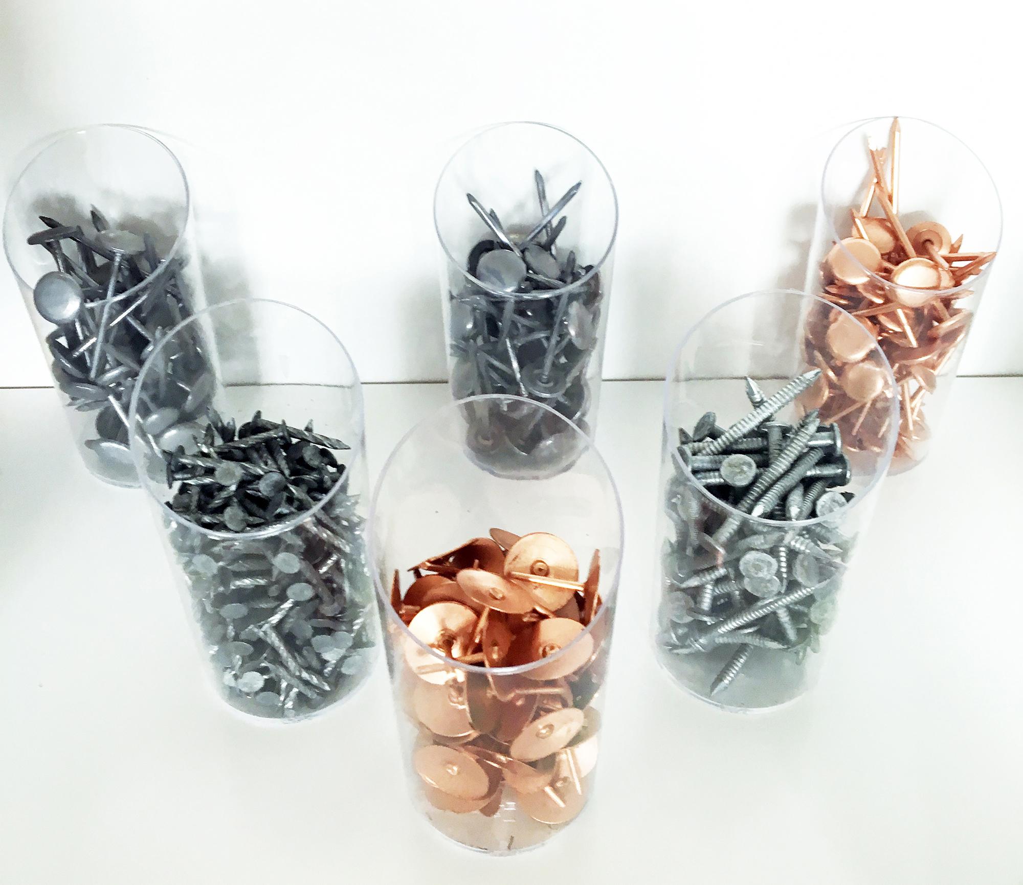 des clous en cuivre et en acier sont disposés dans une série de gobelets en plastqiue trabsparent, posés sur un plan blanc