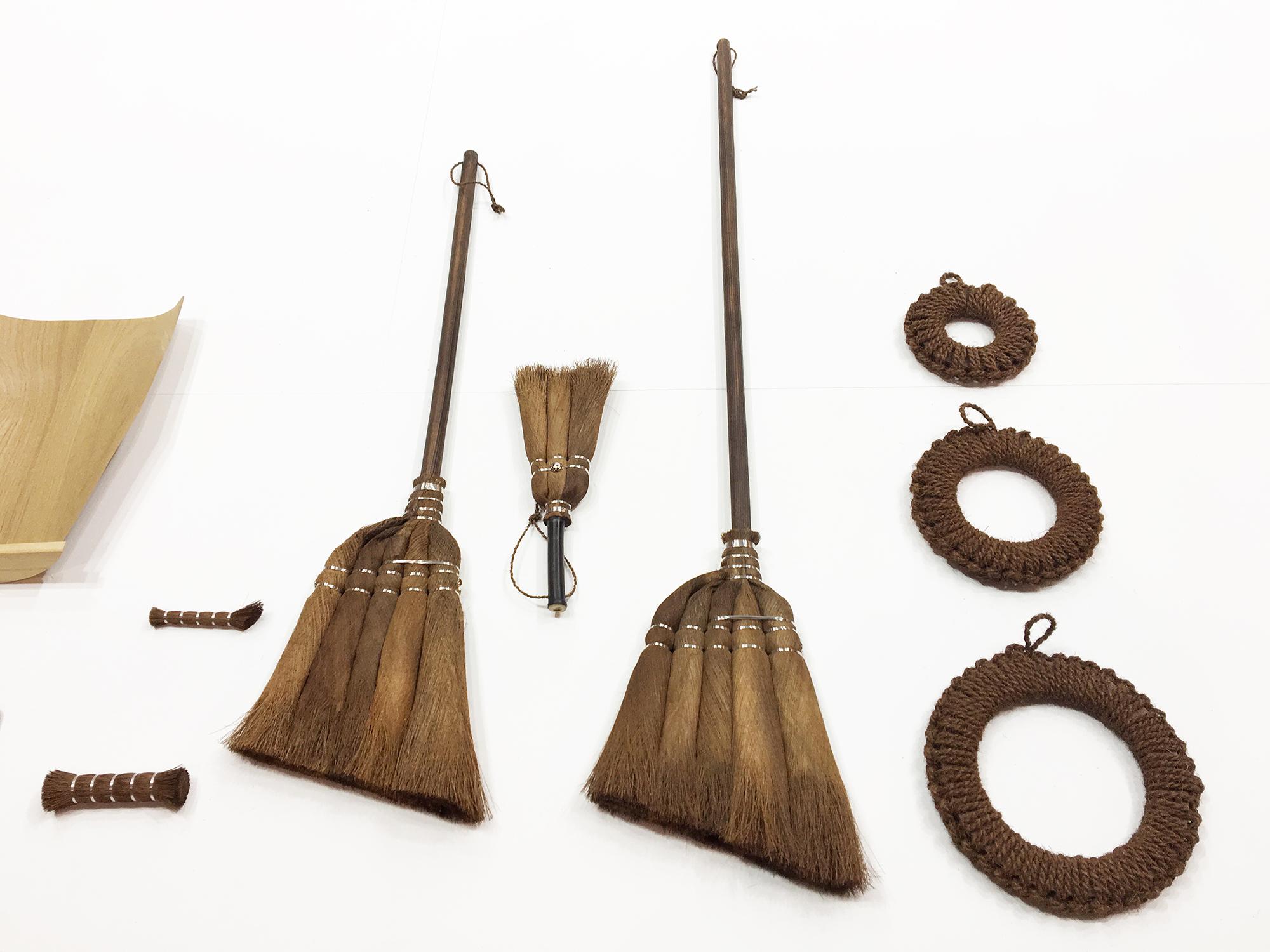 de jolis balais en paille et bois sont exposés sur un fondblanc, comme dans un musée