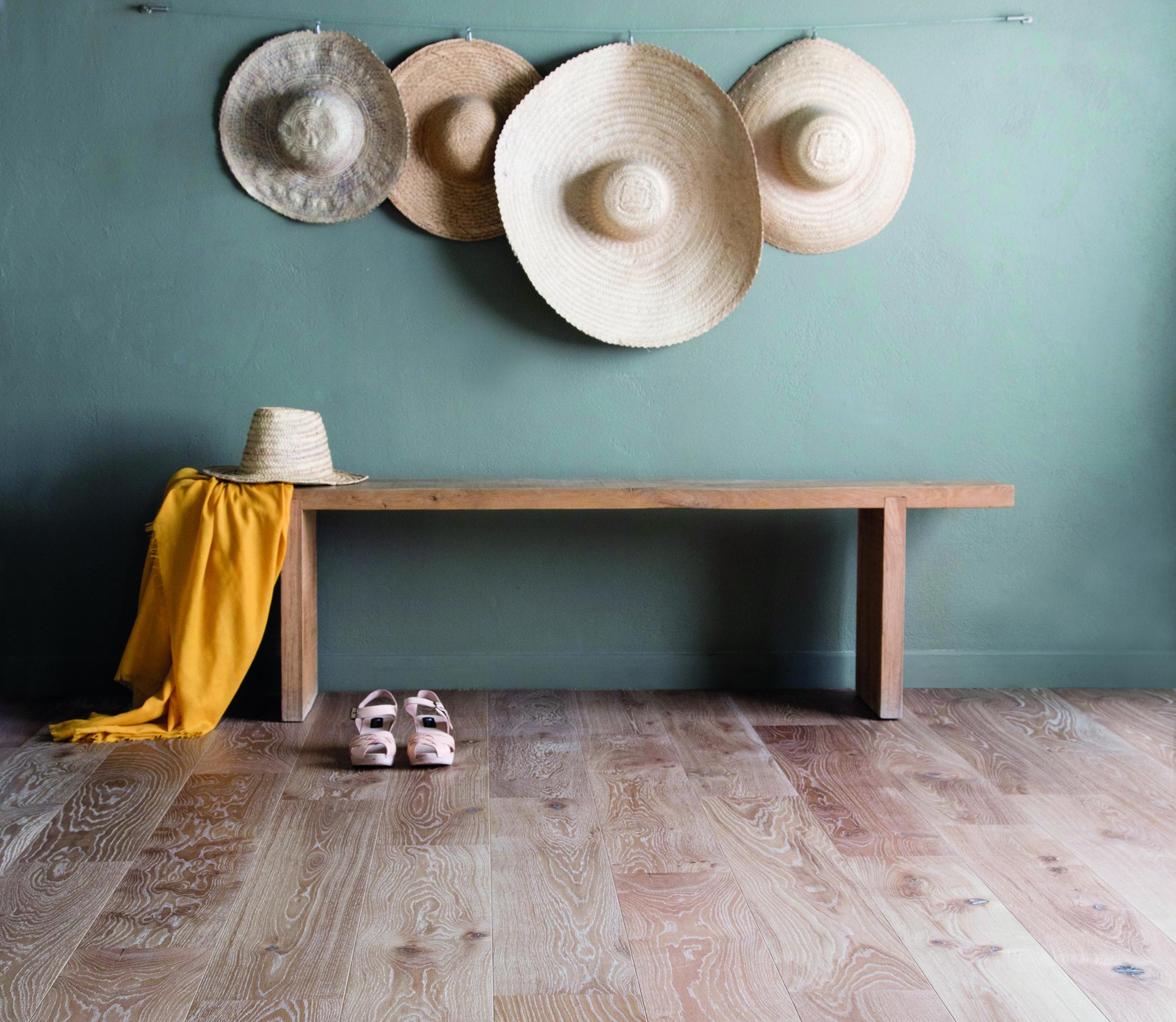 dans une entreé, un banc en bois sur un parquet clair. Le mur peint en vert d'eau accueille 4 grands chapeaux de paille accrochés comme des tabelaux. Un air de printemps