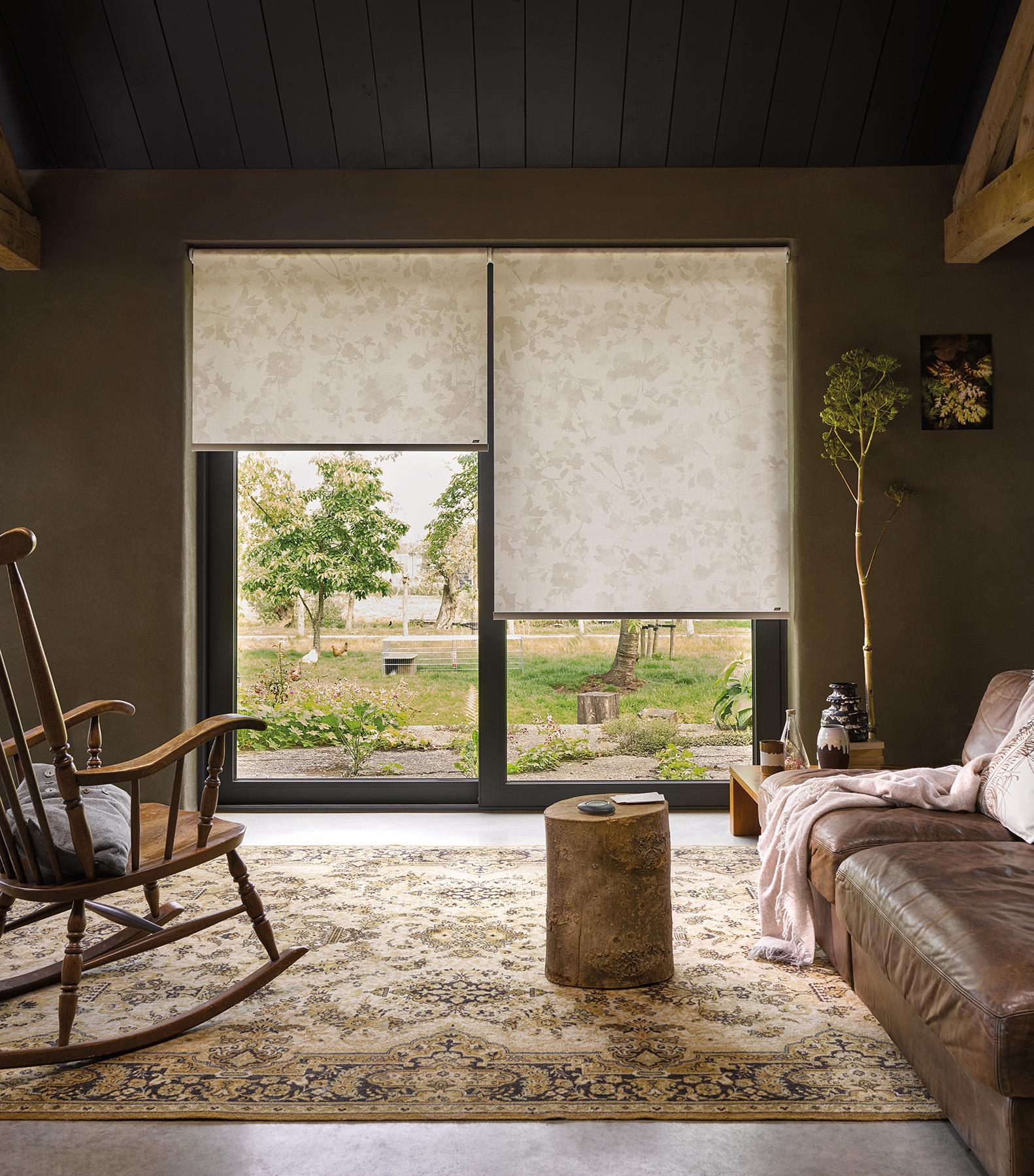 un salon très cosy est équipée de baie vitrée à deux vantaux avec des tsores rouleaux Luxaflex beige à motif végétal pour un air de printemps