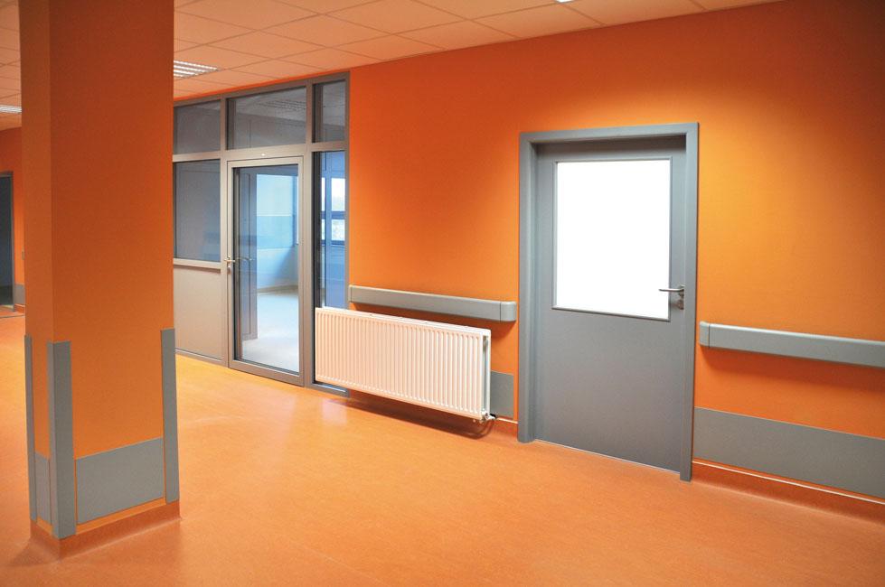 un couloir d'hôpital avec de beaux murs recouverts de toile de verre peinte en orange vif