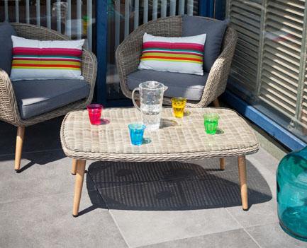 Une terrasse dont l'étanchéité en dalles de grès cérame Siplast, avec unsalon de jardin en rotin. Sur la table une carafe d'eau et de sverres en couleurs.