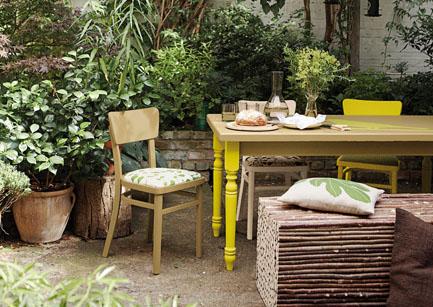 une terrasse aménagée avec une chaise en bois chinée, une table en bois aux pieds tournés et peints en jaune fluo. Peintures Julien