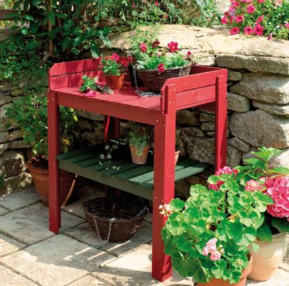 Sur une terrasse extérieure, un petit meuble en bois peint en rouge franmboise devient l'atelier de rempotage. Peintures Julien