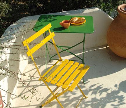 sur une terrasse inondée de soleil, une petite table en fer peinte en vert gazon et une chaise pliante en fer peinte en jaune fluo. Peintures Julien