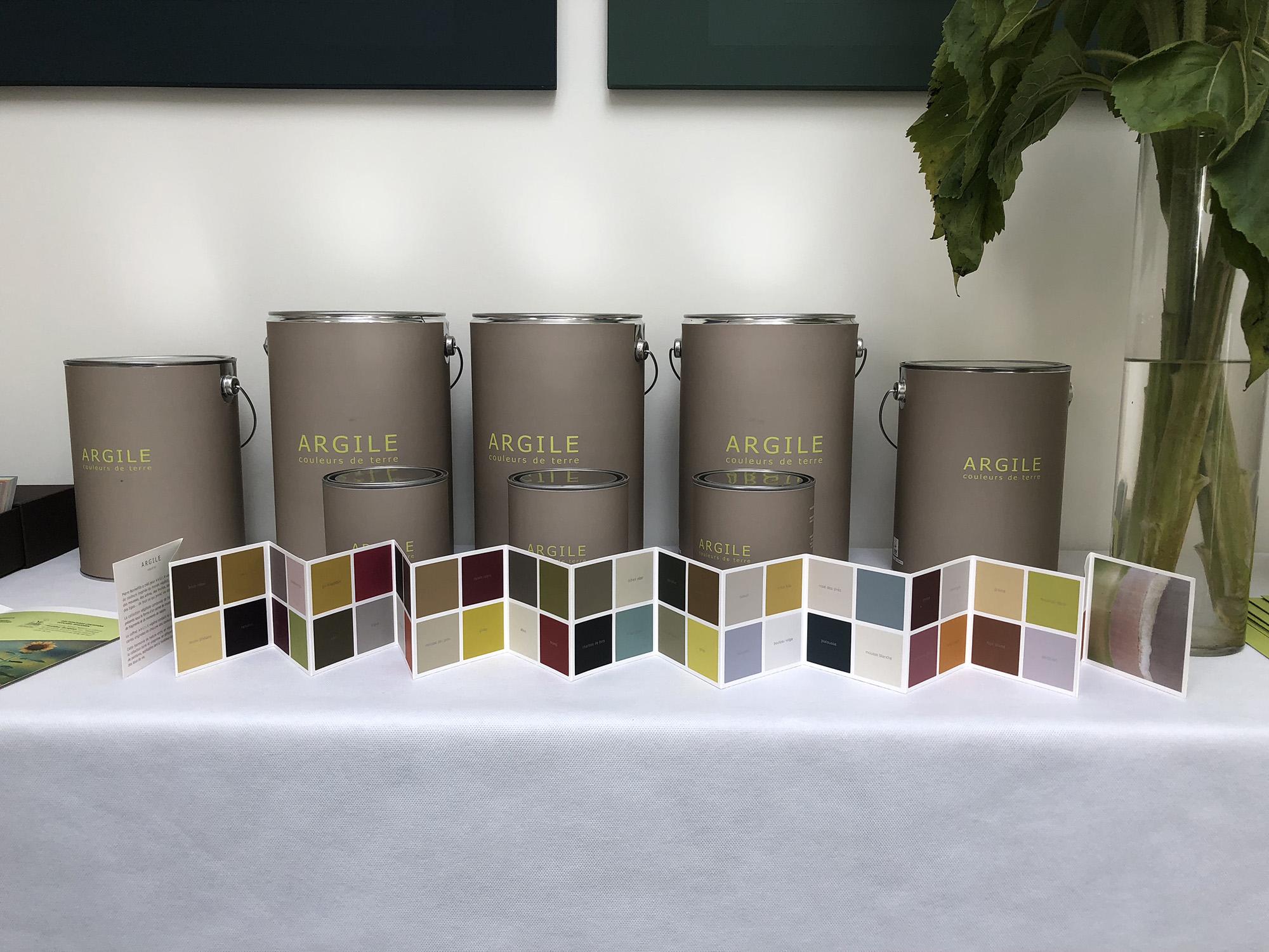 des pots de peintures de la marque Argile derrière des nuanciers de coukeur, sont posés sur une table nappée blanche