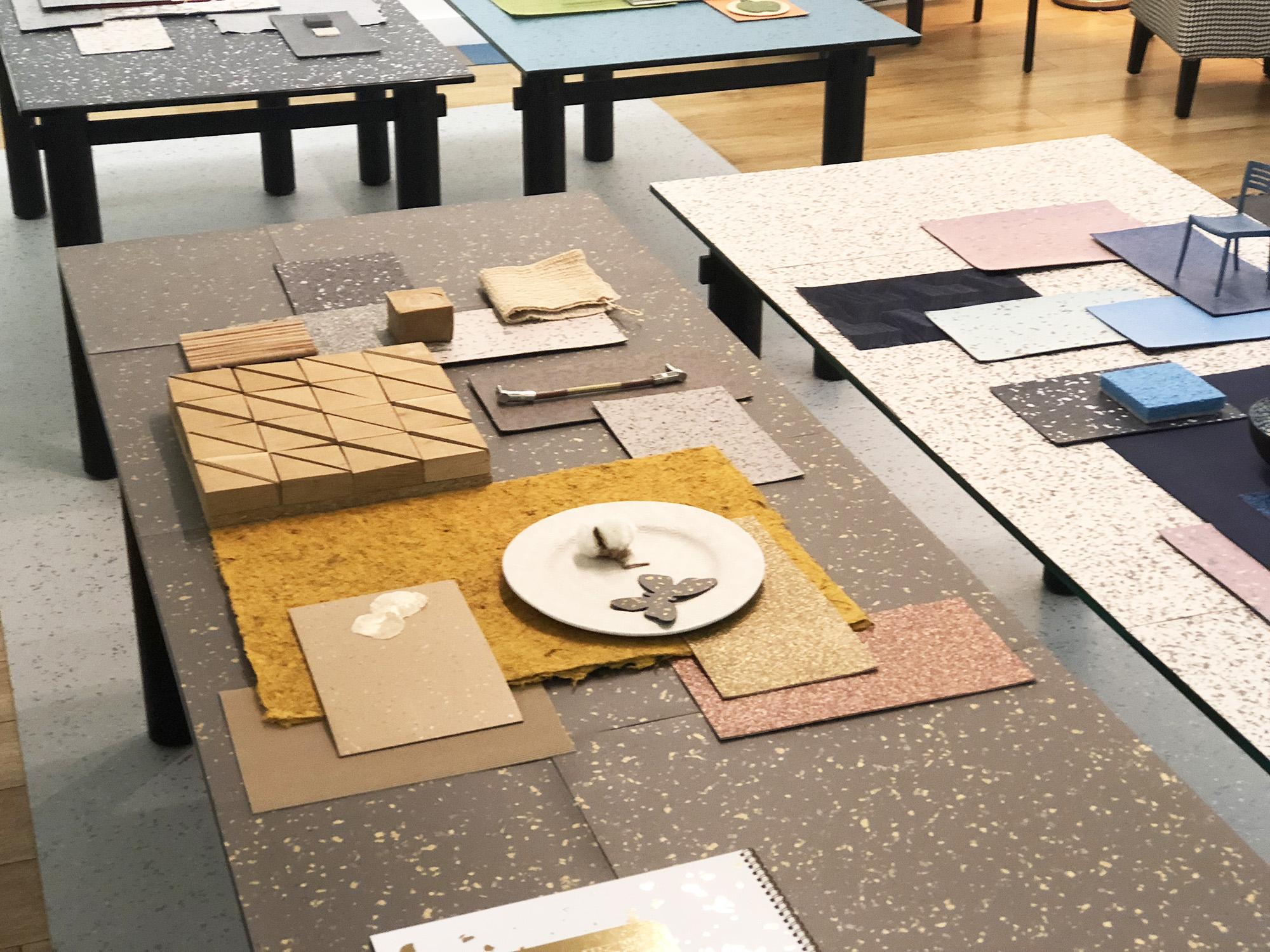 Une table en verre recouverte d'un pêle-même de matériaux dans les tons ocre et doré