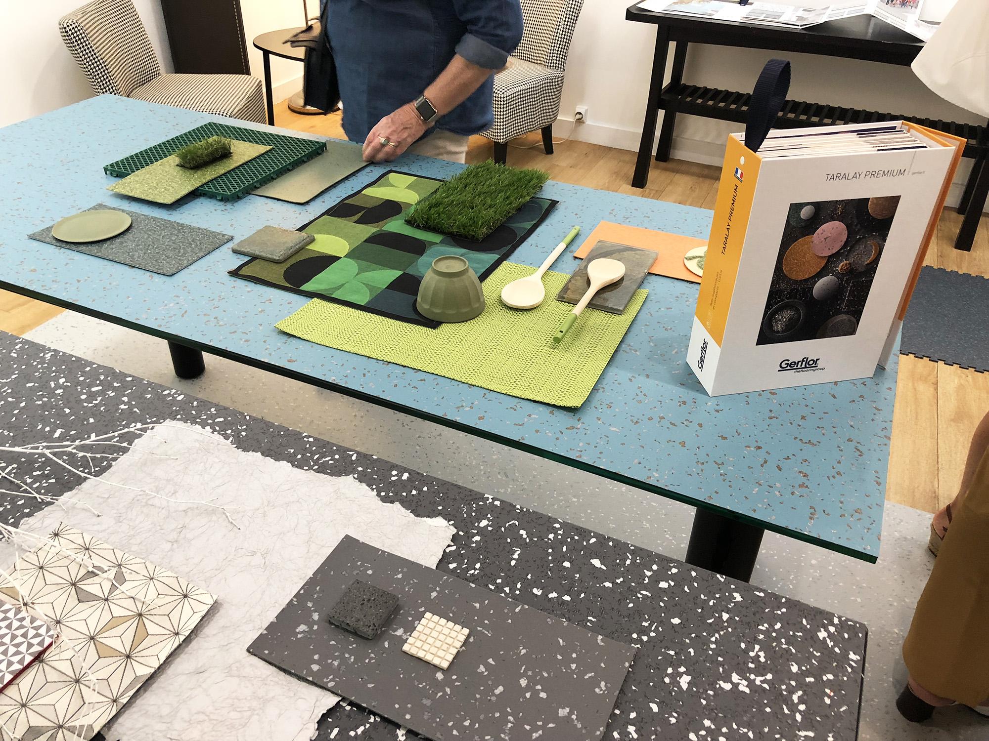 Une table en verre recouverte d'un pêle-même de matériaux dans les tons verts et bleux