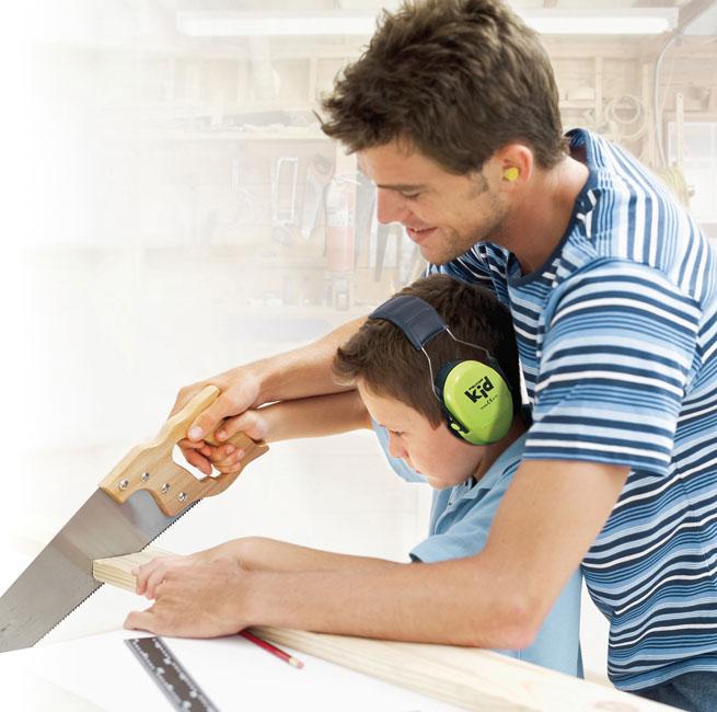 Un papa et son fils bricole ensemble. Ils scient une planche de bois. Le fils porte un casque anti-bruit