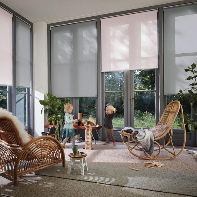Un living très élégant dont les fenêtres sont équipés de stores rouleaux Luxaflex. Deux bambins jouent ensemble