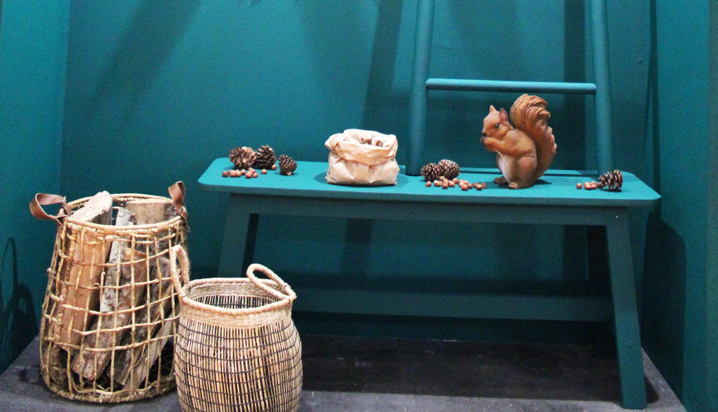 Sur un fond peint en bleu vif, un petit écureuil et de sobjets en raohia sont disposés - espace Virtuous Nelly Rodi - Maiosn & Objet 2018