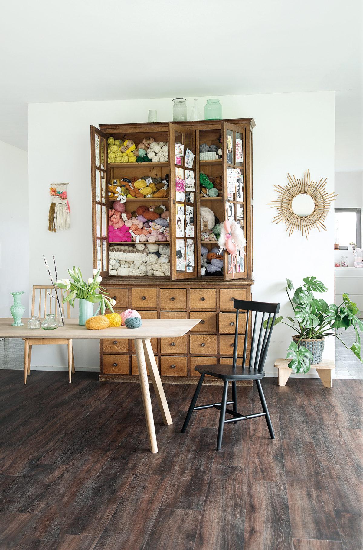 Armoire en bois recyclé qui renferme des pelotes de laine, parquet naturel rustique BerryAlloc, plantes et bouquets, miroir en rotin… une atmosphère Scandicraft.