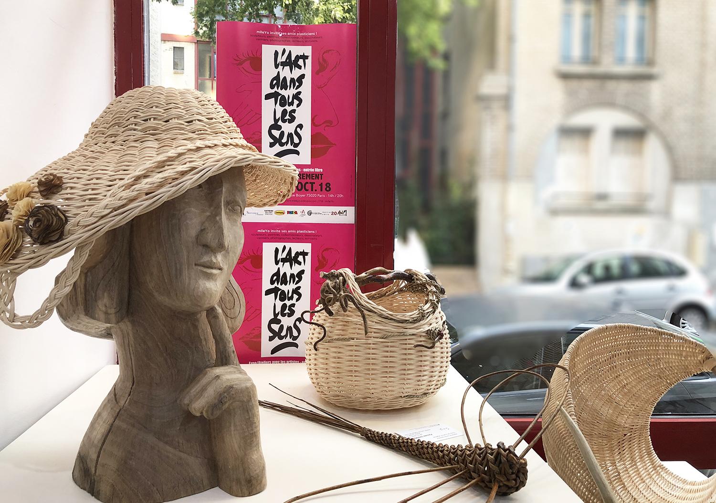"""une tête de femme chapeautée est sculptée dans du bois. À cpoté des sculptres en vannerie. Le tout dans une vitrine sur laquelle est affihcée """"lart dans tous les sens"""""""