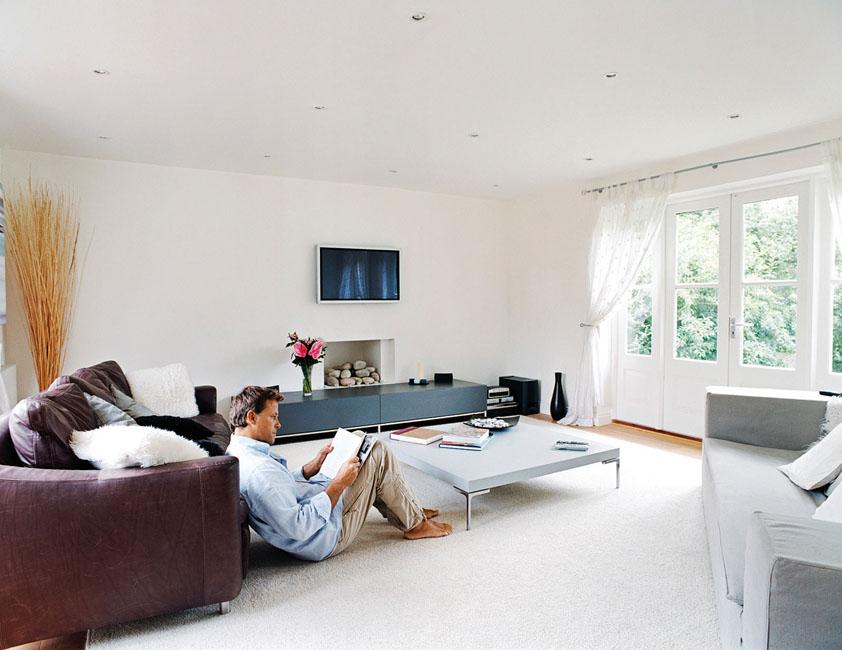 Un homme lit tranquillement dans son salon. Les murs blancs sont enfait des plaques de plâtre qui cachent la technologie Capt'air de Siniat. Elles absorbent la pollution de l'air ambiant.