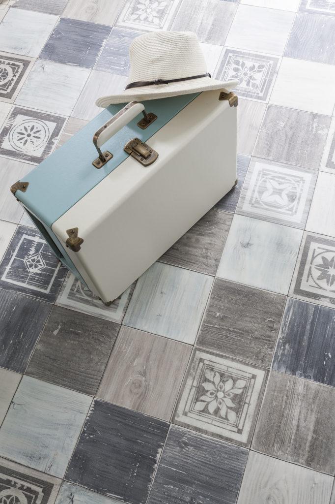 une valise vintage et un panama sont posé surun sol pvc effet carreaux ciment dans les tons bruns, gris et bleu passés.