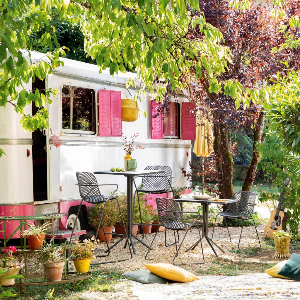 Ambiance bohême avec les chaises Ramatuelle 73' en version hautes et standard. Elles sont posées devant une roulotte aménagée aux volets rose vif, au fond d'un jardin ensoleillé.