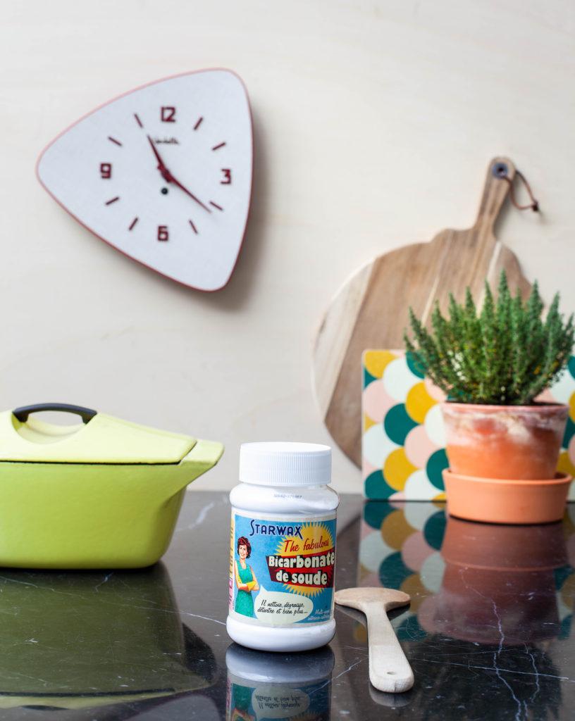 Un pot de bicarbonate de soude est posé sur un plan de travail de cuisine. En arrière plan la déco est vintage avec une pendule des années 50, une cocote en fonte verte et des petits pots de plantes aromatiques.