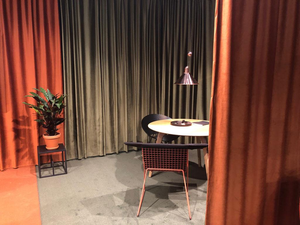 Chez Vzor, une petite table basse et deux fauteuils lovés derrière d'épais rideaux en velours corail
