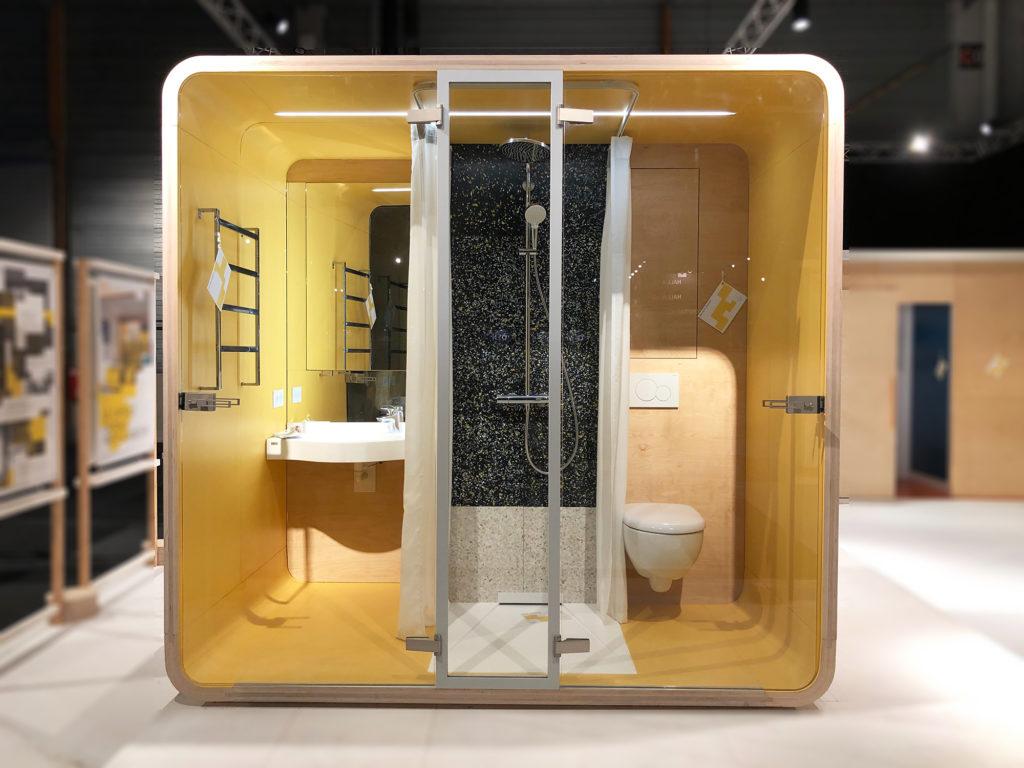 Exposiiton Vivre Bois. Une capsule comportant une salle d'eau complète est exposée au salon Architect@Work. Sa coque est en bois et l'intérieur est laqué jaune. Les sanitaires sont de marque Geberit.