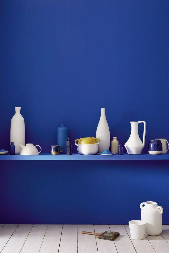 une étagère bleu sur un mur bleu offre un espace d'exposition à différents vases et pichets en céramique